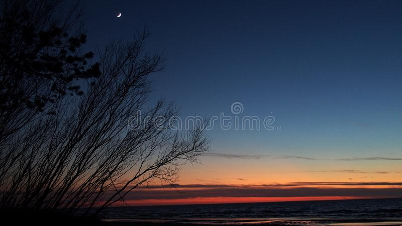 Moon and Venus observing after sunset. Moon, Venus and stars observing, on blue sky, after sunset, over sea royalty free stock photography