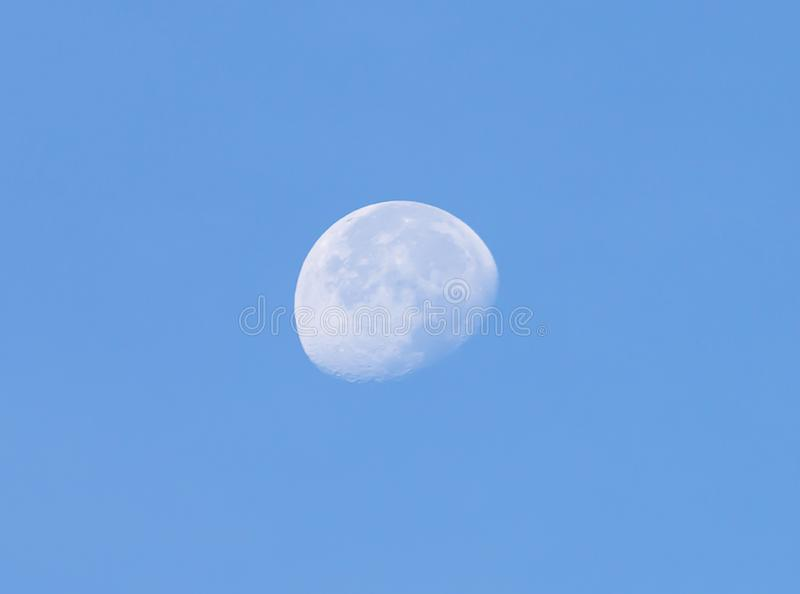 The moon is visible in the morning on a blue background royalty free stock photography