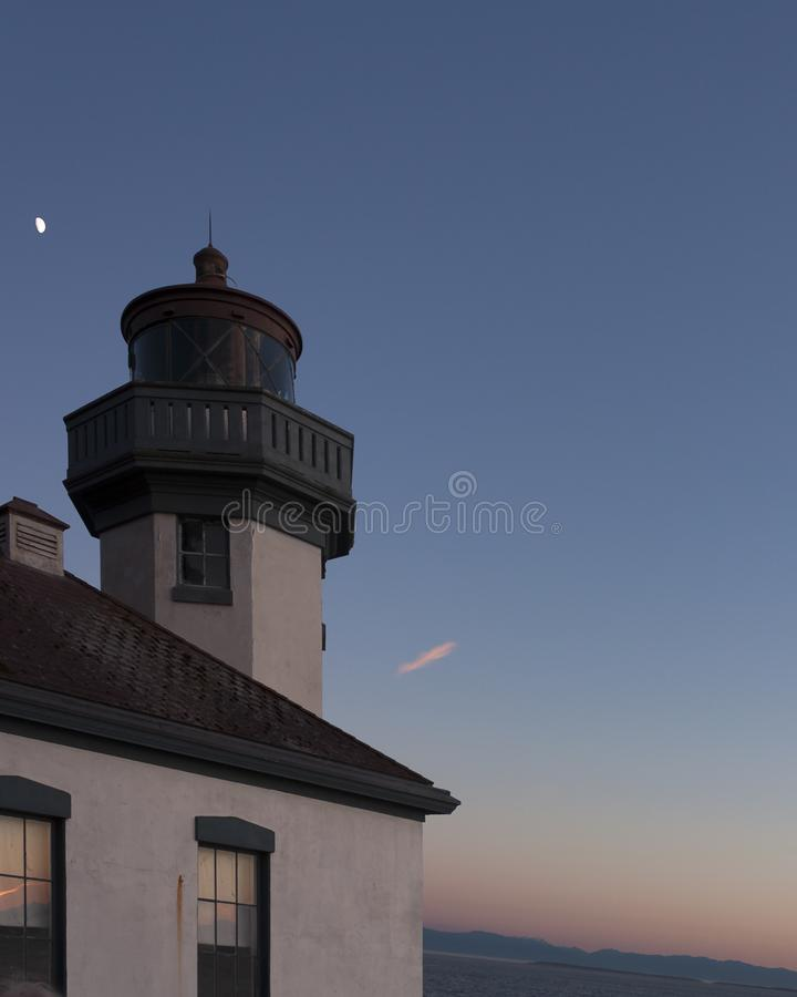 Moon over Lime Kiln Lighthouse. The moon is visible over Lime Kiln Lighthouse on Washington`s San Juan Island royalty free stock photos