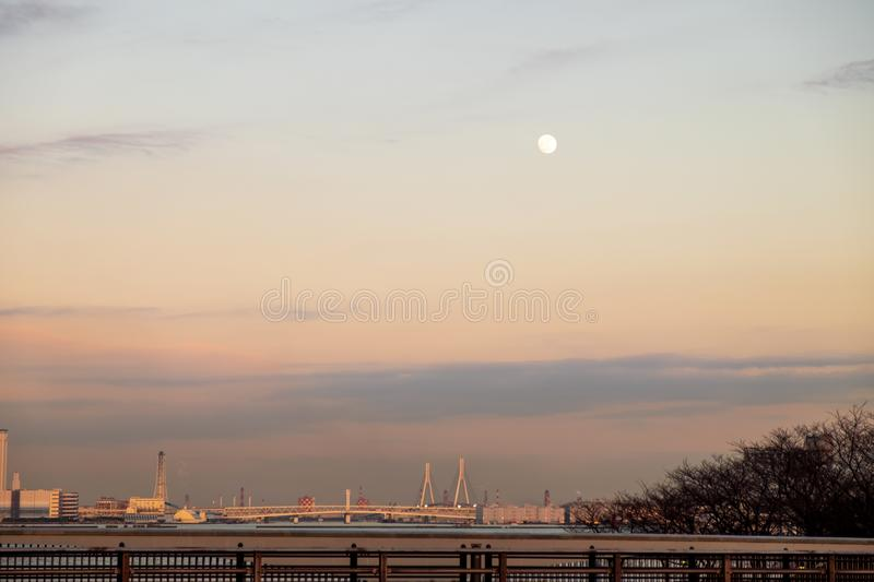 moon was rising over the bridge that crosses the river and buildings in the city royalty free stock image