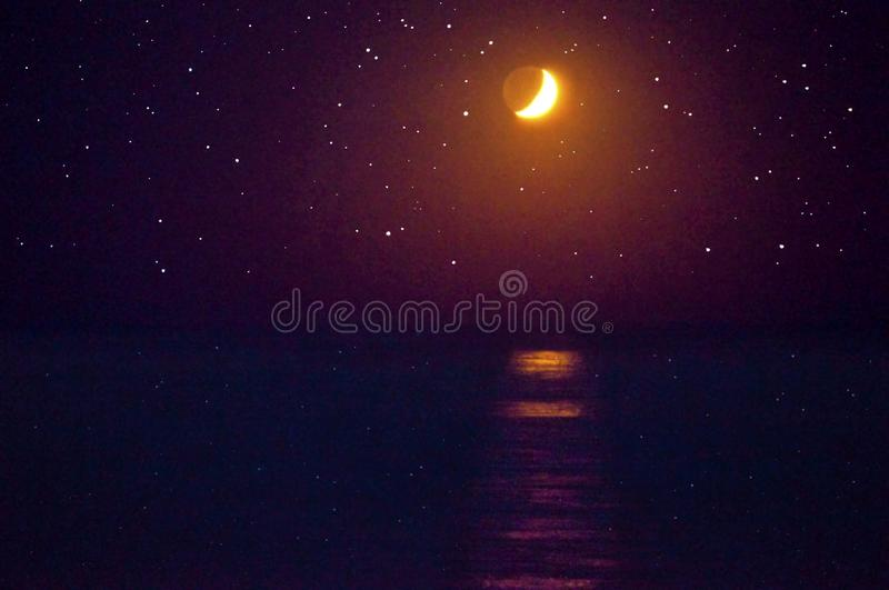 Moon glowing over dark ocean with stars in sky. Moonbeam shines on ocean with stars twinkling in the dark night sky royalty free stock photos