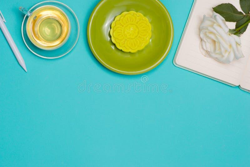 Mooncake de peau de neige et tasse de thé avec des fleurs sur le fond foncé photographie stock libre de droits