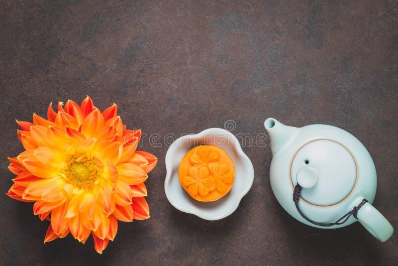 Mooncake, fleurs oranges fraîches de dahlia, une théière bleue et tasses de thé vert sur un fond brun Nourriture chinoise de fest photographie stock