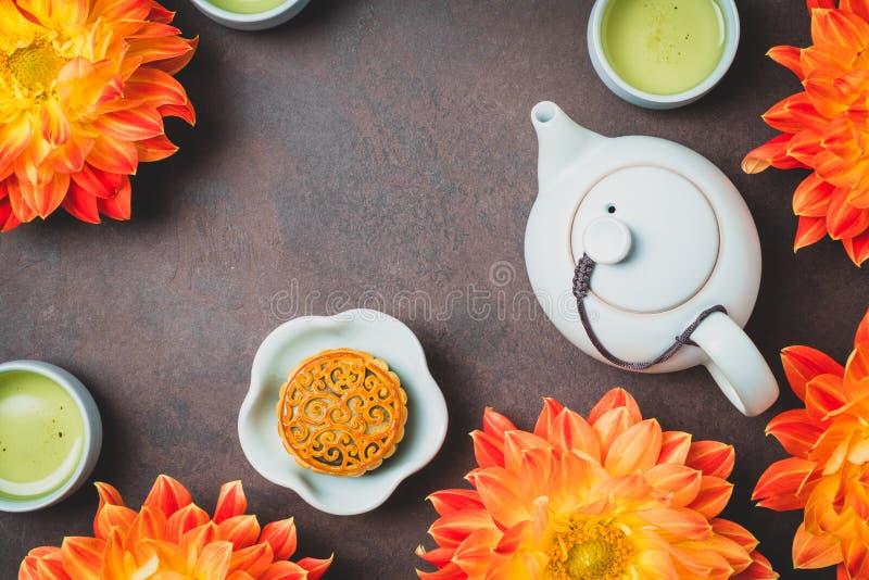 Mooncake, fleurs oranges fraîches de dahlia, une théière bleue et tasses de thé vert sur un fond brun Nourriture chinoise de fest image stock