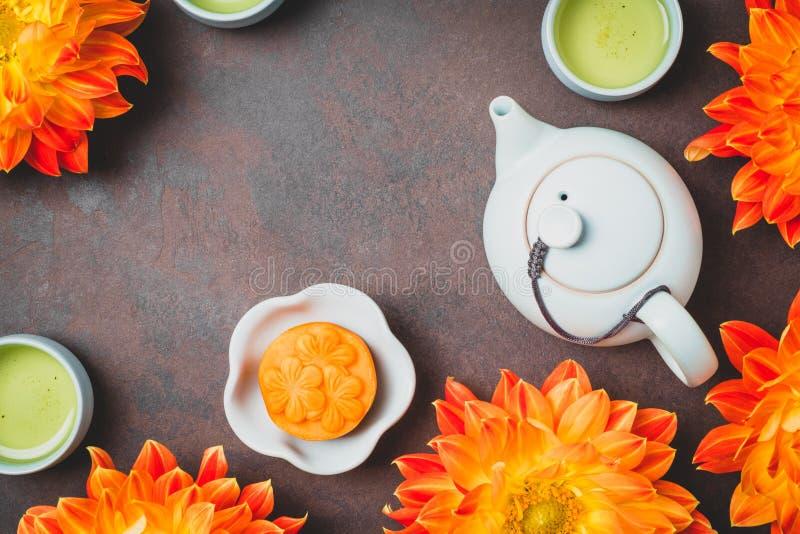Mooncake, fleurs oranges fraîches de dahlia, une théière bleue et tasses de thé vert sur un fond brun Nourriture chinoise de fest photos libres de droits