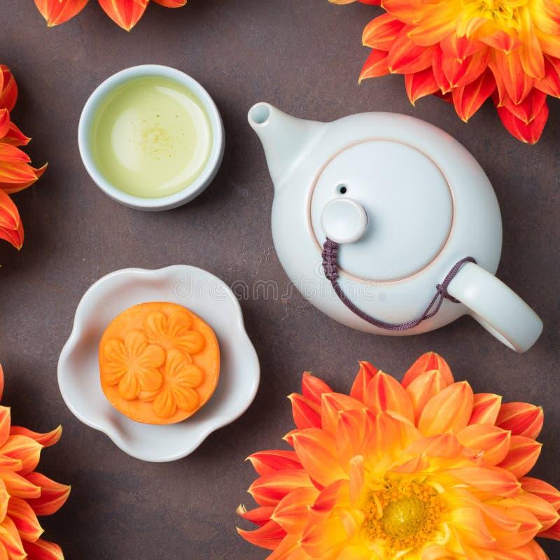 Mooncake, fleurs oranges fraîches de dahlia, une théière bleue et tasses de thé vert sur un fond brun Nourriture chinoise de fest image libre de droits