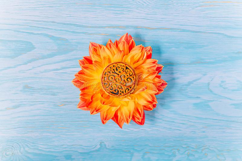 Mooncake in a fresh orange dahlia flower on a blue wooden background. Chinese mid-autumn festival food royalty free stock photo