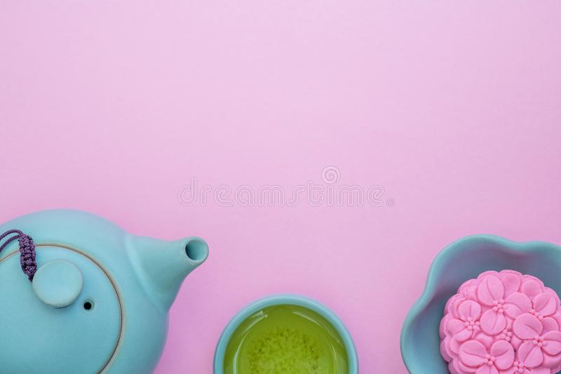 Mooncake rose, théière bleue, tasse de thé vert sur un fond rose Nourriture chinoise de festival de mi-automne photographie stock