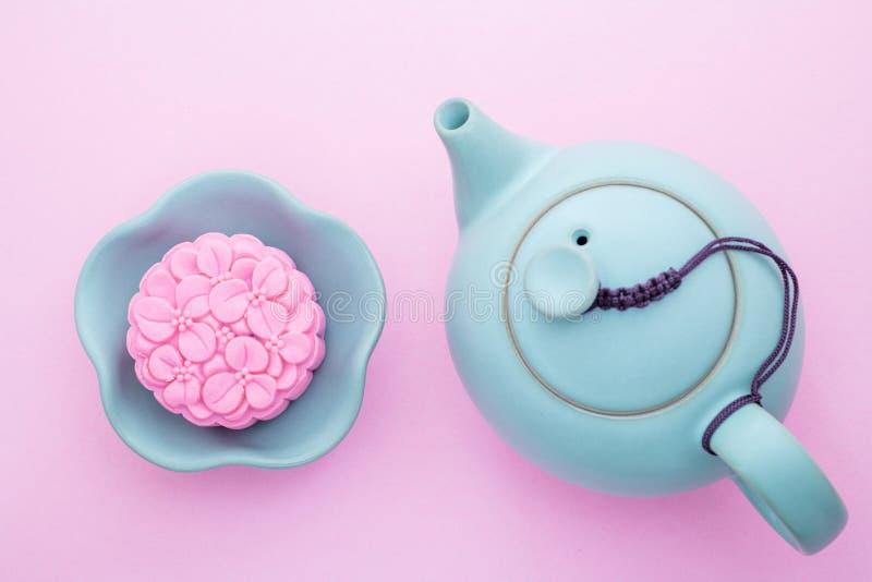 Mooncake rose, théière bleue, tasse de thé vert sur un fond rose Nourriture chinoise de festival de mi-automne images libres de droits