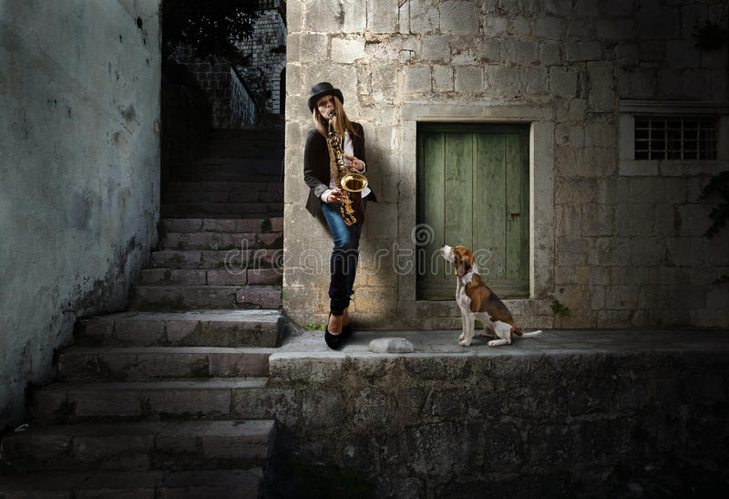 Moonlight blues. Young beautiful woman in black hat with saxophone