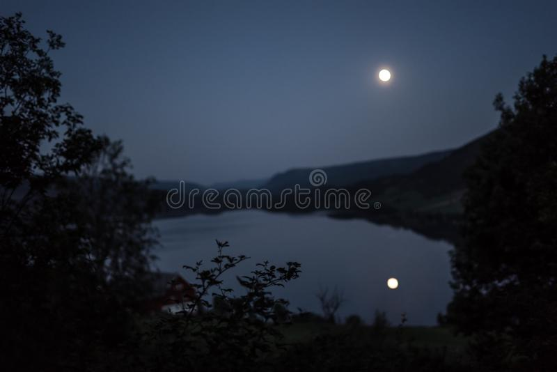 Moonlight from a glowing fullmoon reflected in a lake at midnight with mountains and trees around. A dark, mystical moonlit pond in a quiet, romantic seascape at royalty free stock images