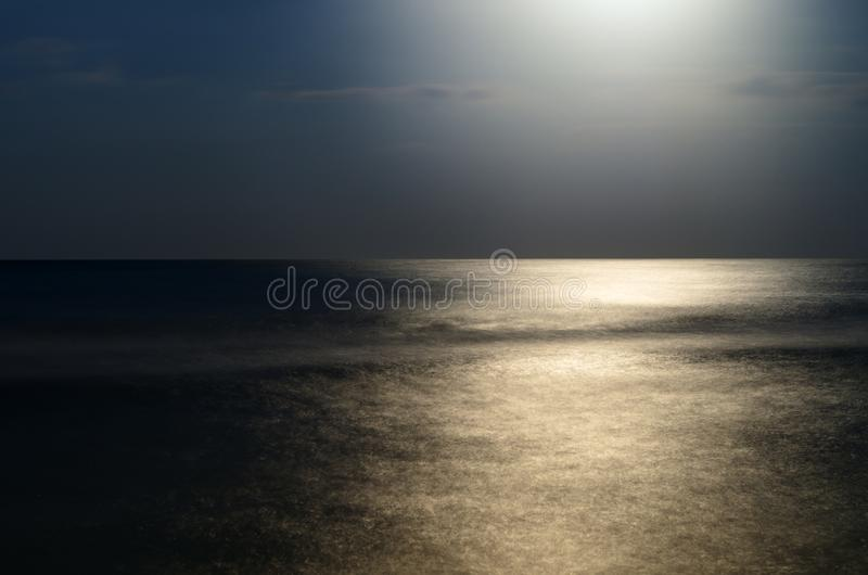Moonlight at night over the sea, reflection. horizon blue sky with clouds royalty free stock photography