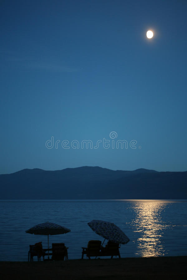 Moonlight on water by beach. stock photos