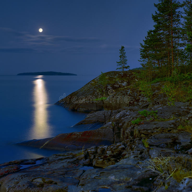 Moonlit night at stony shore of Ladoga lake stock images