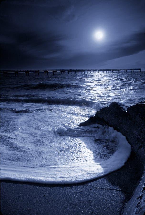 Moonrise markerar den runda havvågen och pir i golf av Mexico royaltyfri foto