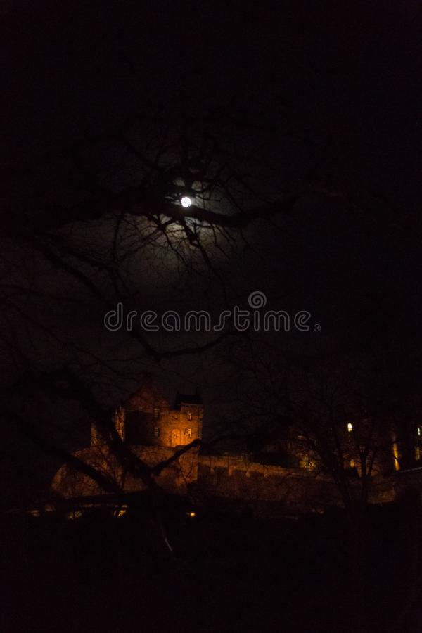 Moonrise ovanför Edinburgslott i Skottland på natten arkivfoto