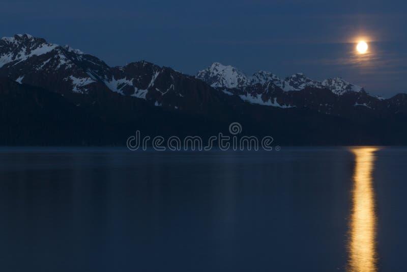 Moonrise over bergen met volle maanbezinning stock foto