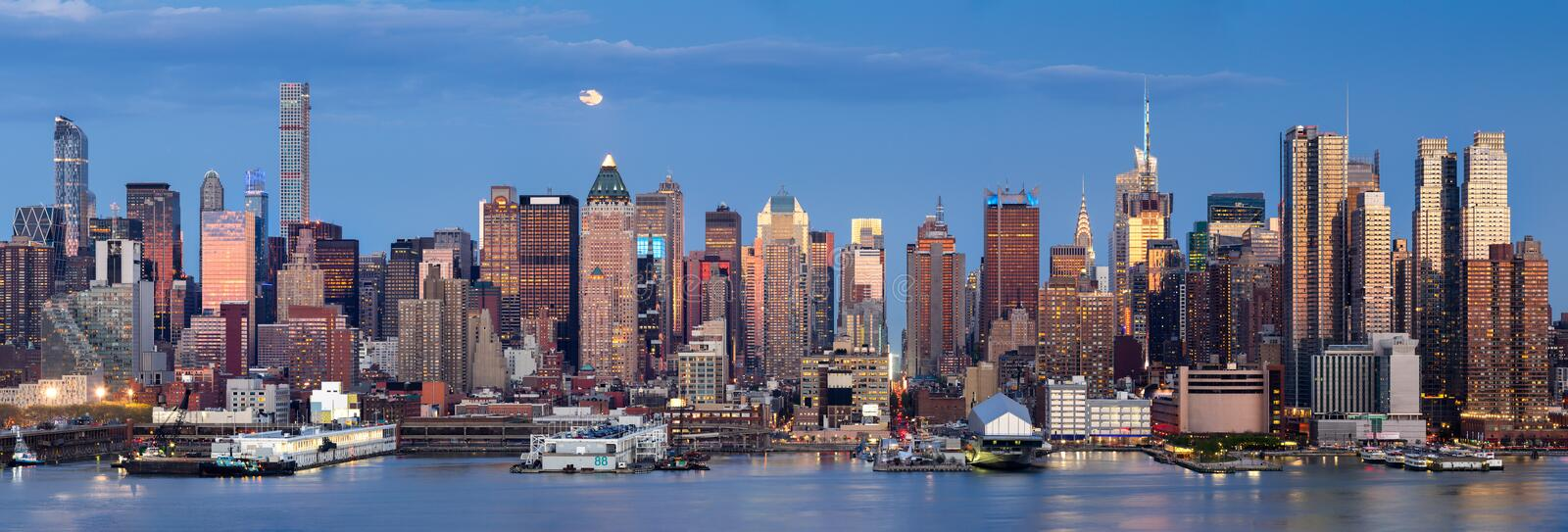 Moonrise over Midtown West with Manhattan skyline, New York City. Midtown West Manhattan skyscrapers over the Hudson River. Panoramic view in early evening with stock photo