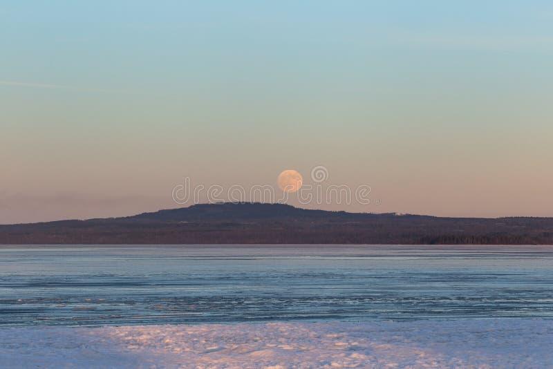 Moonrise over mountain Kinnekulle in sweden stock photo