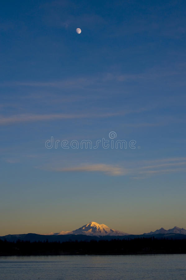 Moonrise over Mt. Baker. The almost full moon rises over Mt. Baker in the Puget Sound area of western Washington State. Taken from Lummi island in the San Juan royalty free stock photo