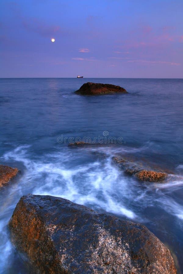 Moonrise over the ocean stock photos