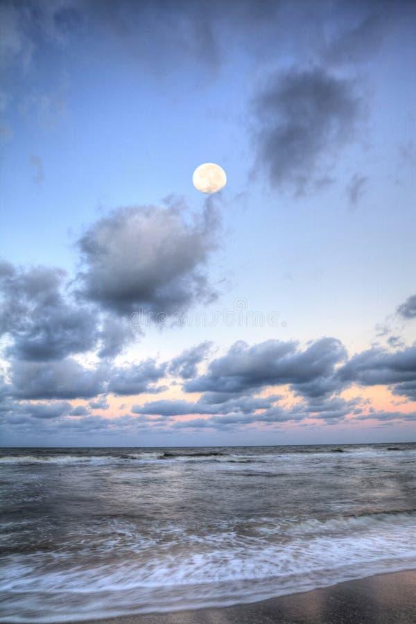 Moonset über dem Ozean an Vanderbilt-Strand bei Sonnenuntergang lizenzfreies stockbild