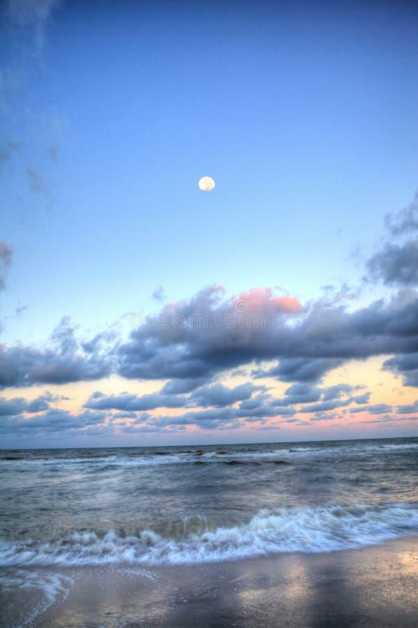 Moonset über dem Ozean an Vanderbilt-Strand bei Sonnenuntergang lizenzfreie stockfotos