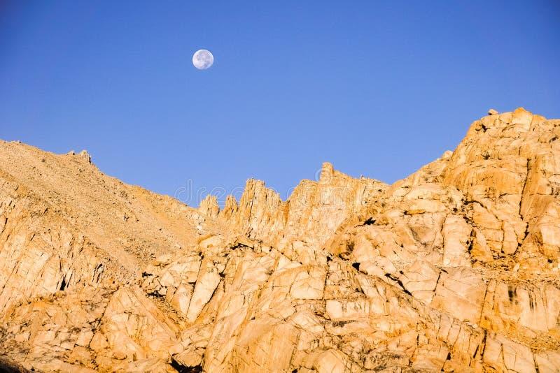 Moonset atrás de uma montanha rochosa no nascer do sol, serra oriental montanhas, montagem Whitney Trail, Califórnia fotos de stock royalty free
