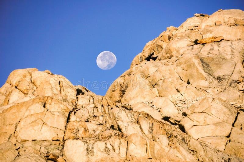 Moonset atrás de uma montanha rochosa no nascer do sol, serra oriental montanhas, montagem Whitney Trail, Califórnia fotografia de stock