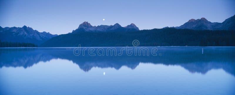 Moonset au lever de soleil au-dessus du lac redfish photos stock