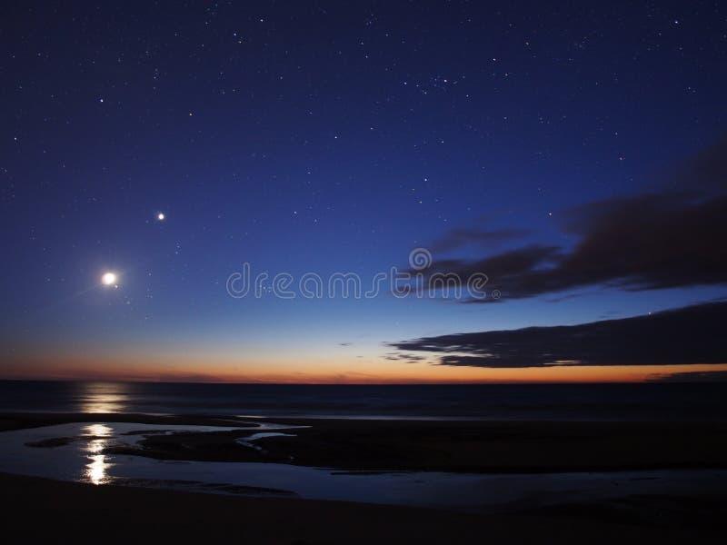 Moon Venus and stars on night sky stock image