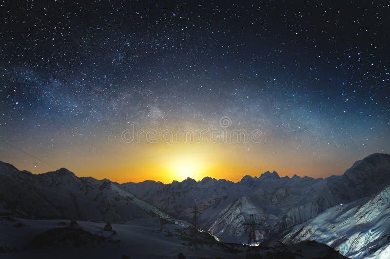 Moonset nas montanhas na noite com uma Via Látea horizontal no céu Picos cobertos de neve das montanhas na noite foto de stock