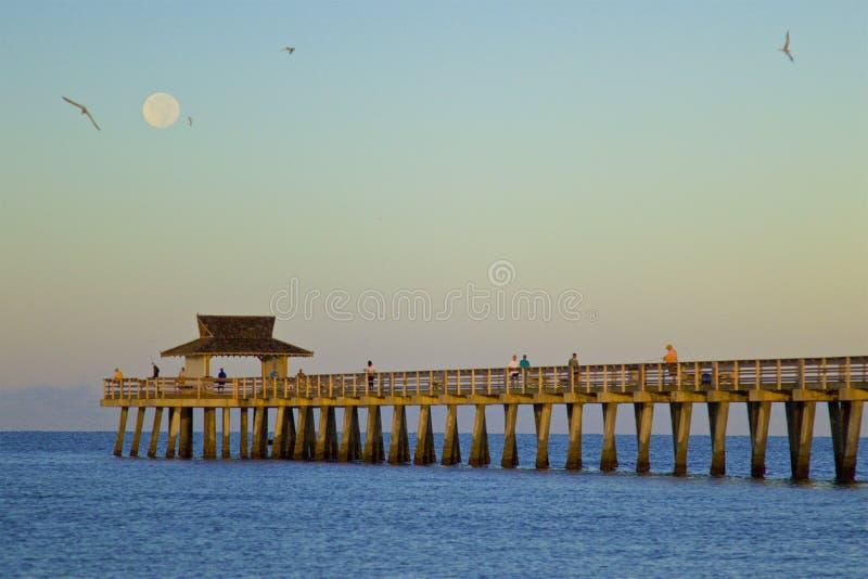 Moonset at sunrise stock images