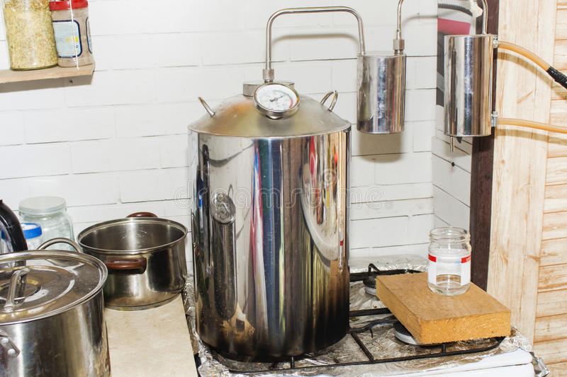 Moonshine still in action, at home. Alcohol mashine stock photo