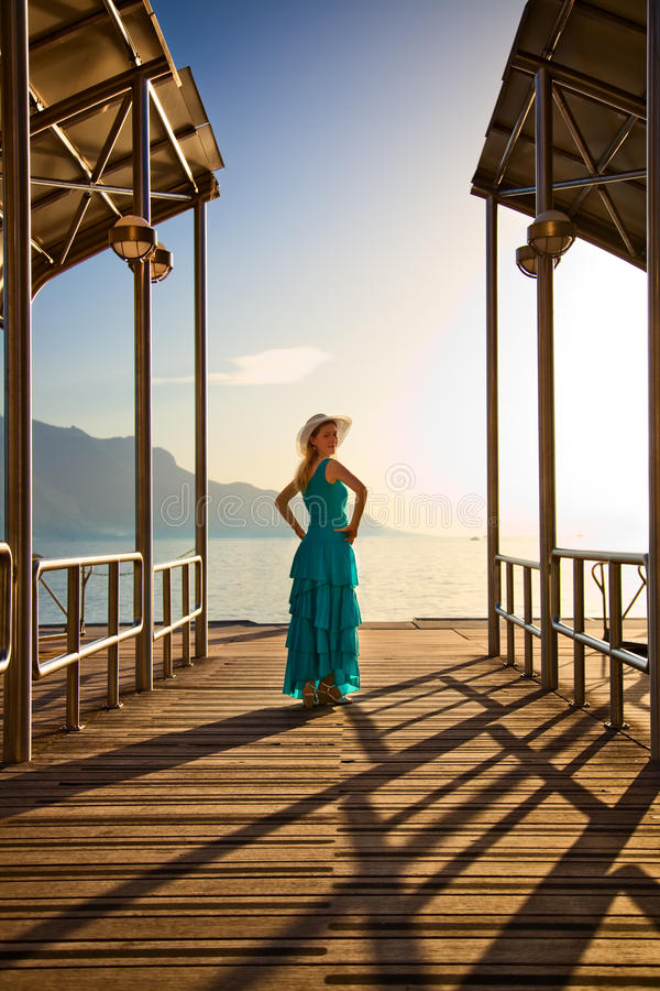 At the moorage. Young woman in blue dress standing at the moorage royalty free stock images