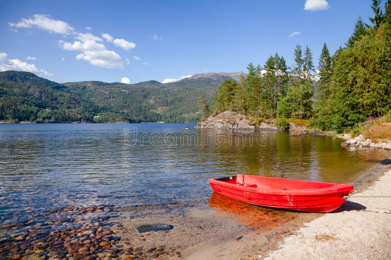 Moored boat at Lake in Norway. Small red plastic boat moored on a lake shore in Telemark County, Norway, on a bright sunny summer day stock images