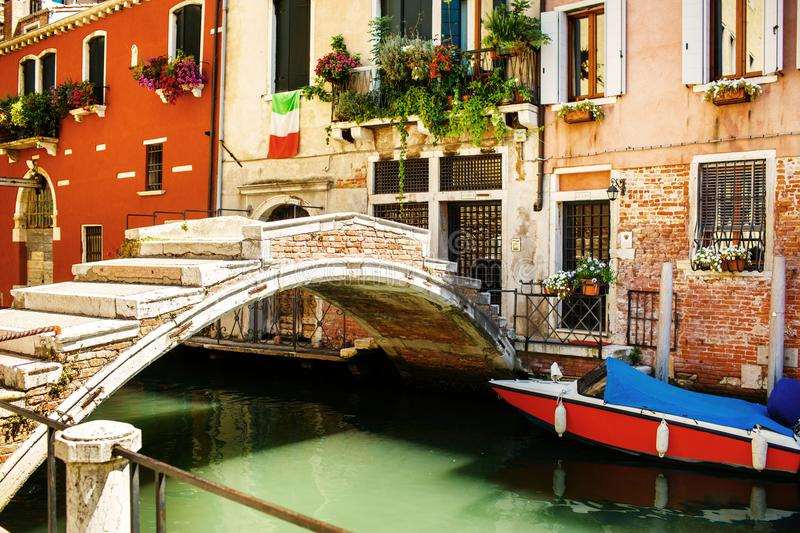 The moored boat next to the colorful house and bridge. Canals in Venice, Italy royalty free stock image