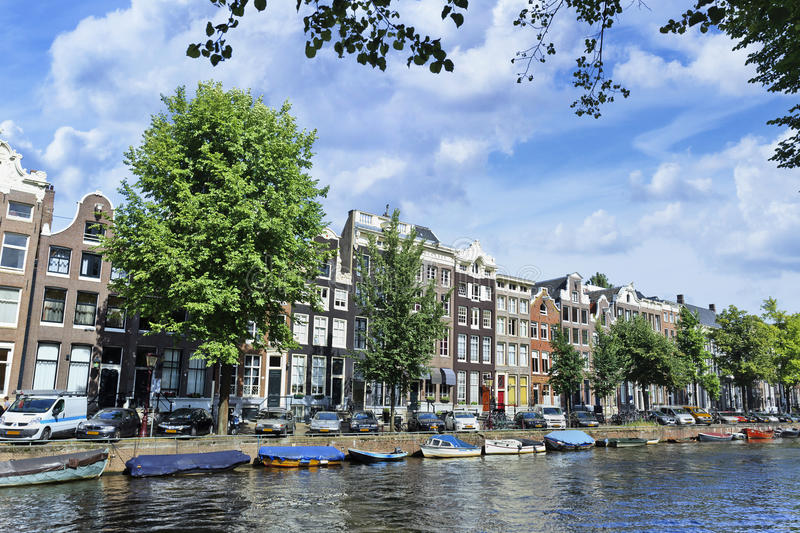 Moored boats and ancient gabled houses in Amsterdam stock image
