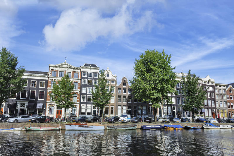 Moored boats and ancient gabled houses in Amsterdam royalty free stock image
