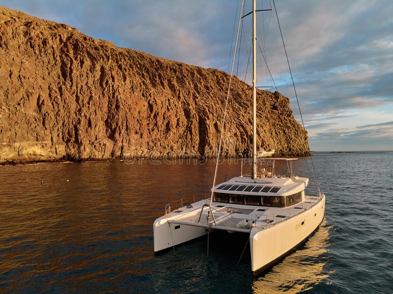 Moored lonely modern catamaran in calm waters of Atlantic Ocean near rocky volcanic cliff royalty free stock photography