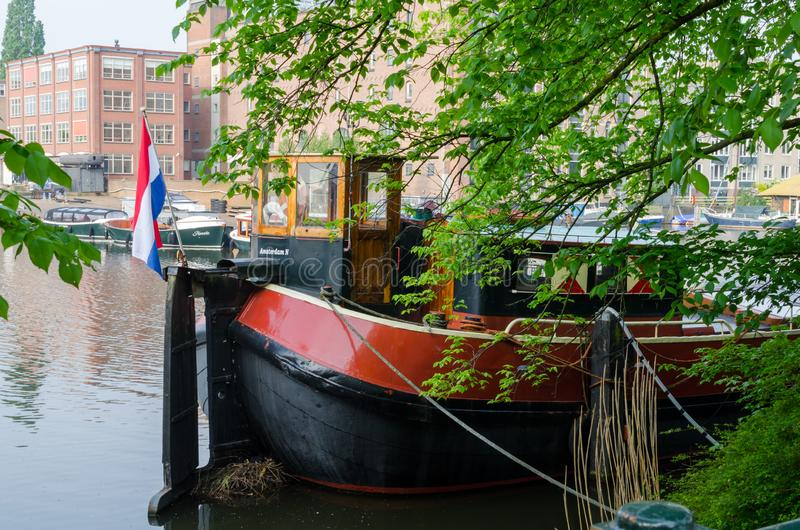 Moored old retro ship with the flag of the Netherlands on the channel in the Amsterdam.  royalty free stock photography