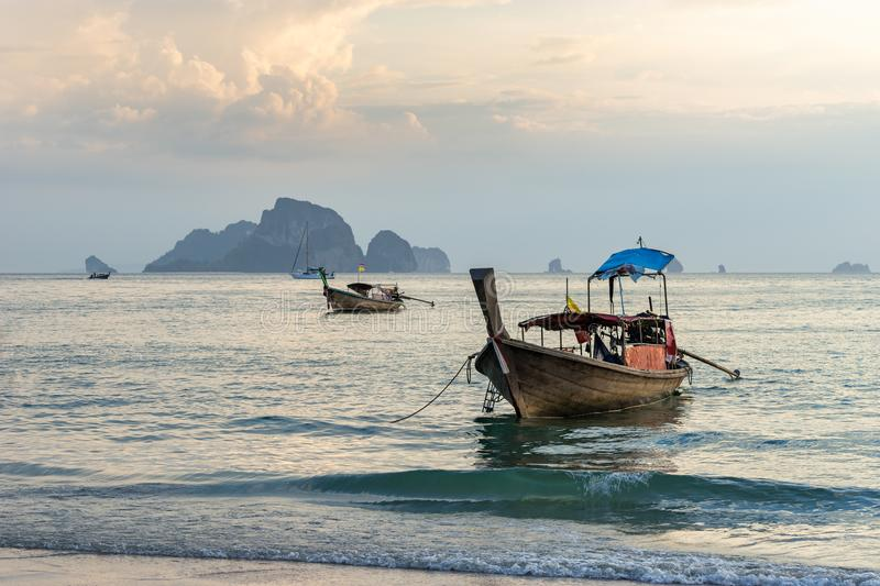 Thai traditional long-tail boat in the sea water near the shore in the evening on Ao nang beach in Krabi province. Moored thai traditional long-tail boat in the stock image
