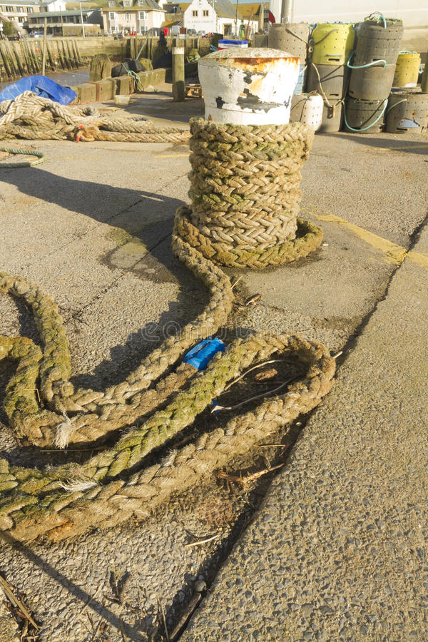 Mooring bollard with rope, West Bay. Thick Rope partially wound around ship's mooring bollard, West Bay, Bridport, England, United Kingdom, Europe stock photo