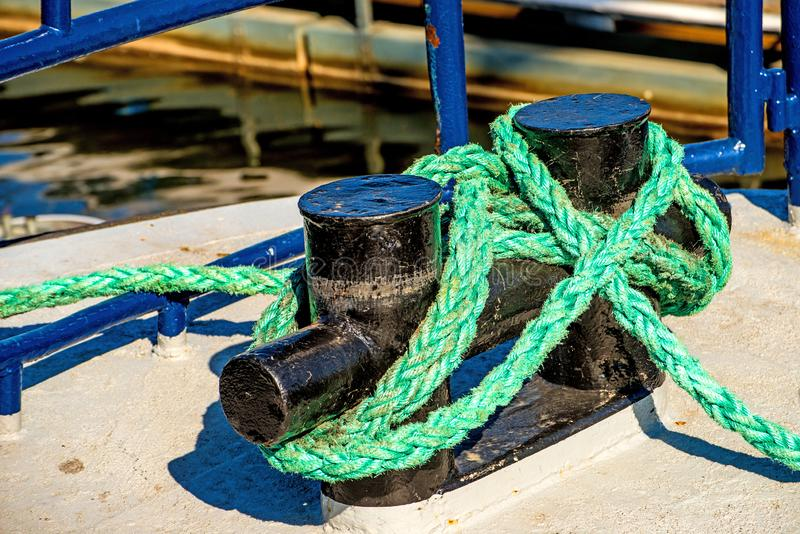 Mooring line of a trawler on blue cleats. In a port royalty free stock photos