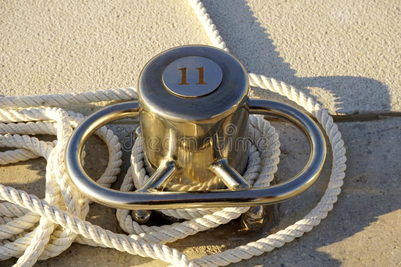 Mooring pillar number eleven for mooring yachts in marine, with white rope and made from stainless steel. Number eleven on the stainless steel mooring pillar for royalty free stock photo