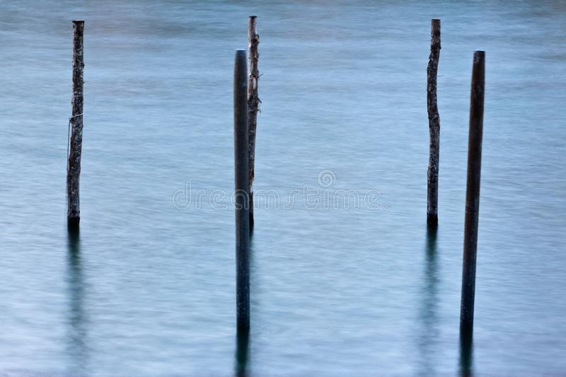 Mooring post water Venice, Venzia, Italy, Italia. Wooden beams of mooring posts, bollards or dolphins in the water canal of Venice, Venezia, Italy, Italia stock photos
