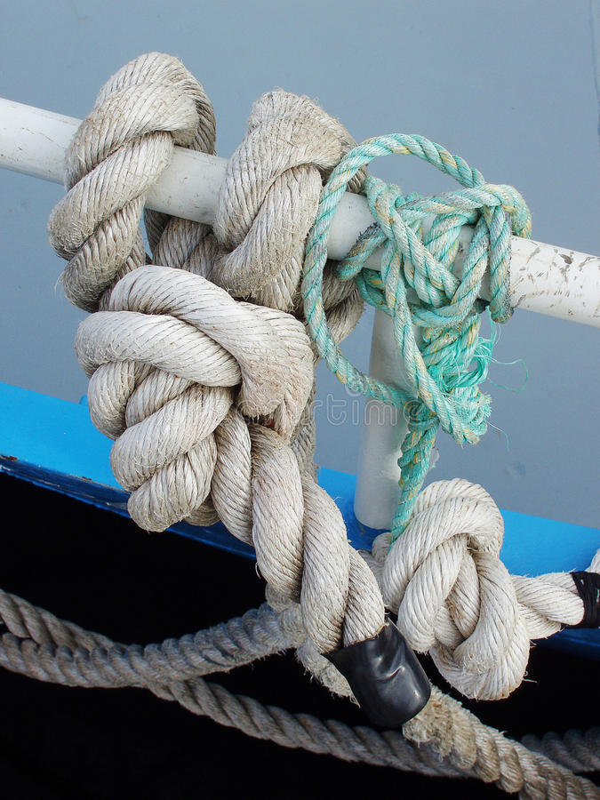 Mooring Rope. Heavy duty mooring rope tied to fishing boat railing stock photo