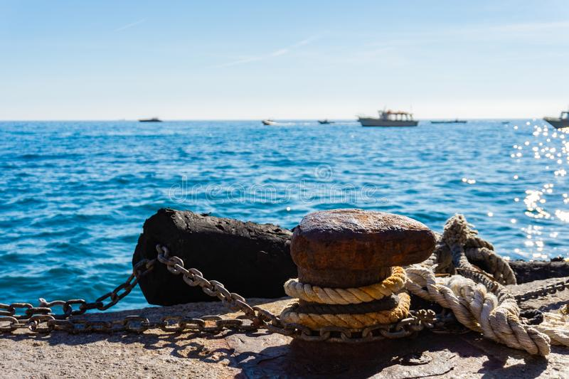 Mooring rope and old bollard on sea water and yachts background stock image