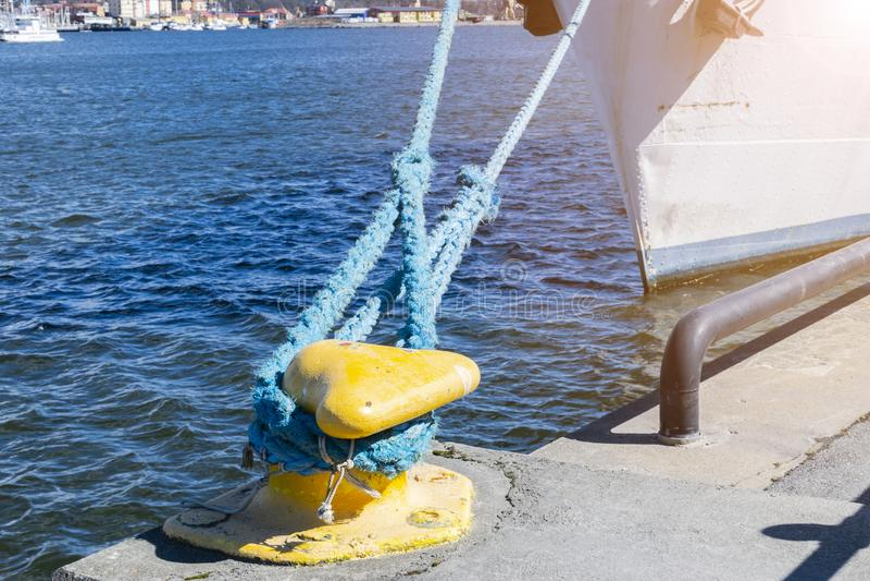 Mooring rope tied to the bollard at the pier.Nautical mooring rope. Shipping objects concept. Sailing ropes. Yellow marina bollard stock photos