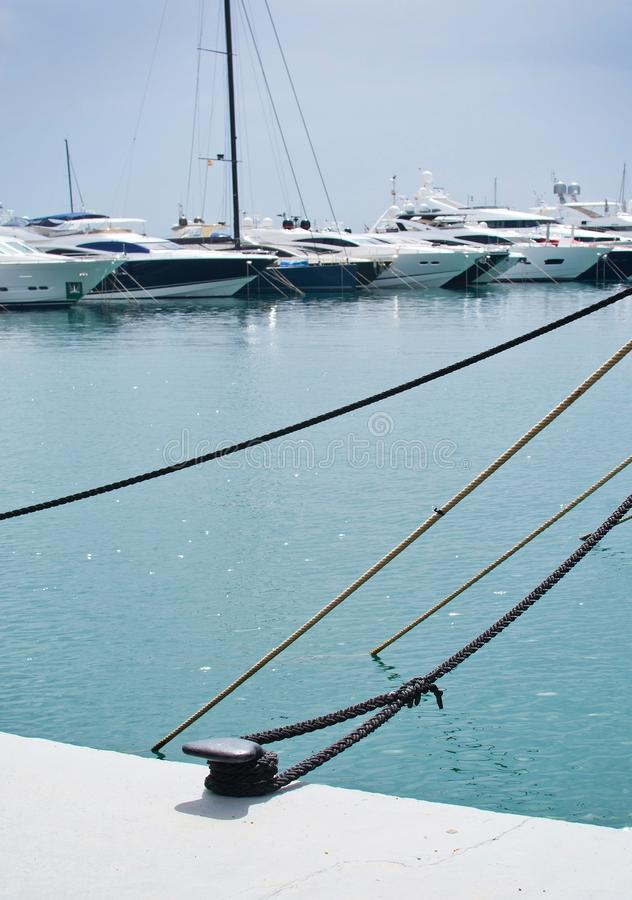 Mooring ropes against Mediterranean gree. PUERTO PORTALS, MALLORCA, SPAIN - APRIL 24, 2018: Luxury yachts moored in the marina of Puerto Portals on an overcast royalty free stock photography
